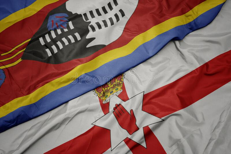 waving colorful flag of northern ireland and national flag of swaziland stock photo