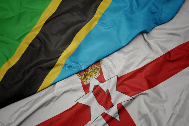 waving colorful flag of northern ireland and national flag of tanzania royalty free stock image