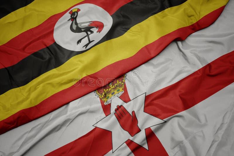 waving colorful flag of northern ireland and national flag of uganda royalty free stock photography