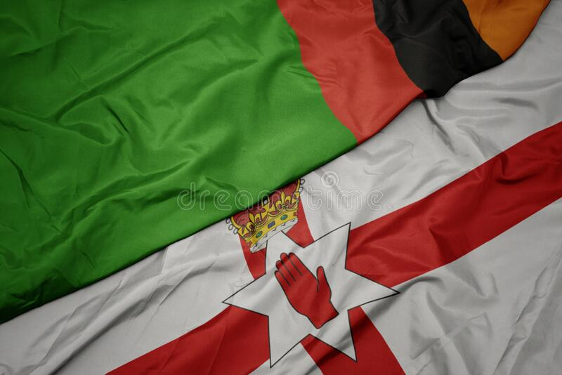 waving colorful flag of northern ireland and national flag of zambia royalty free stock photography