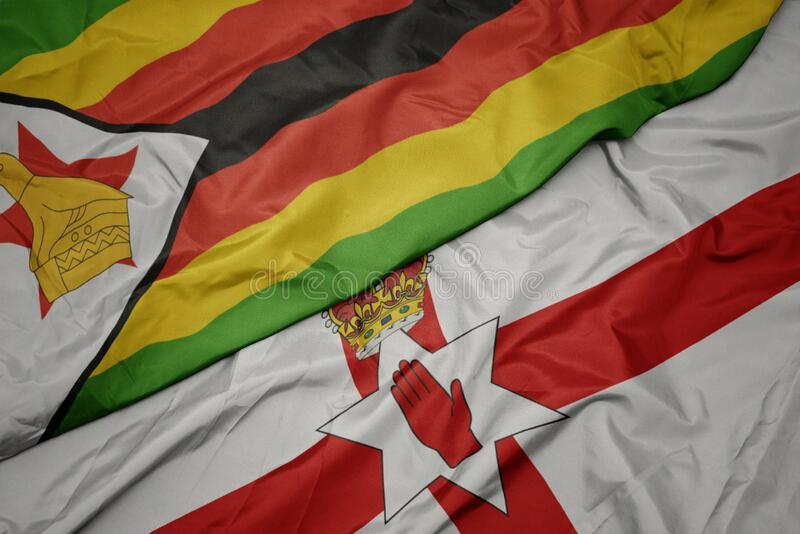 waving colorful flag of northern ireland and national flag of zimbabwe royalty free stock photo