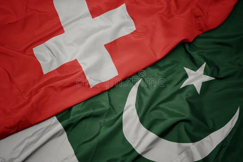Waving colorful flag of pakistan and national flag of switzerland. Macro royalty free stock photos