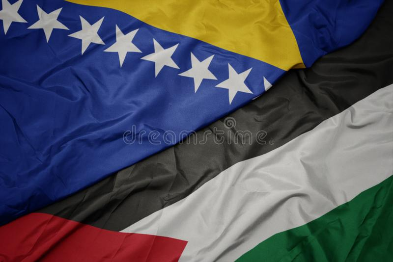 Waving colorful flag of palestine and national flag of bosnia and herzegovina. Macro stock image