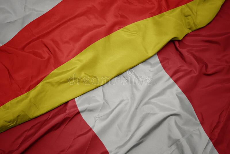 Waving colorful flag of peru and national flag of south ossetia. Macro stock photography