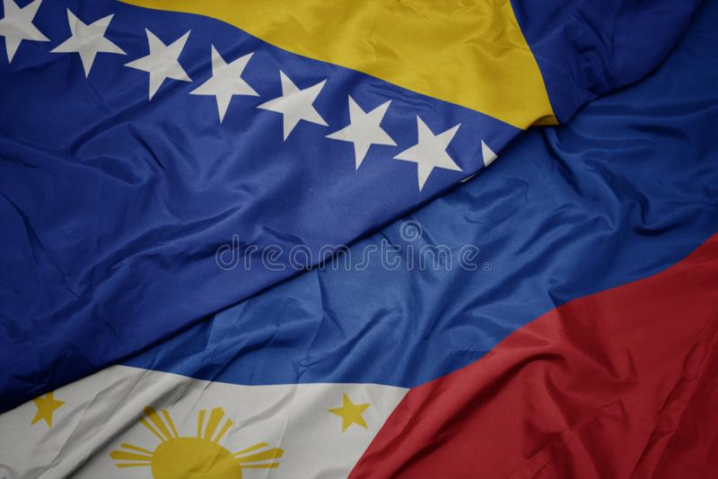 Waving colorful flag of philippines and national flag of bosnia and herzegovina. Macro royalty free stock images