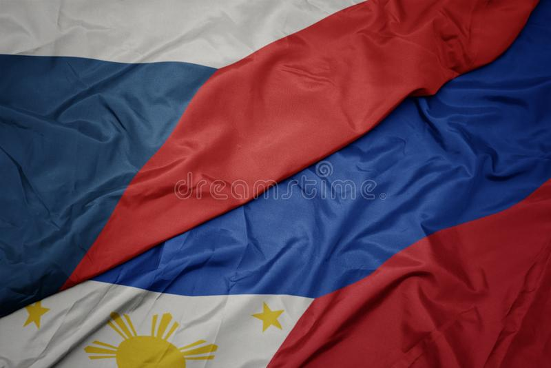 Waving colorful flag of philippines and national flag of czech republic. Macro stock photo