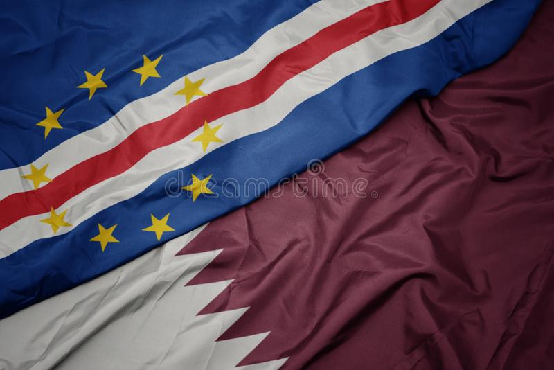 Waving colorful flag of qatar and national flag of cape verde. Macro royalty free stock photo