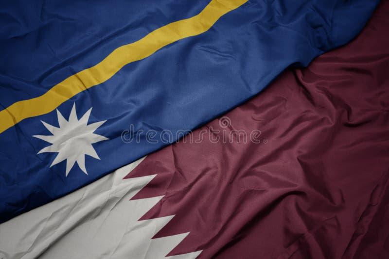 Waving colorful flag of qatar and national flag of Nauru. Macro stock photos
