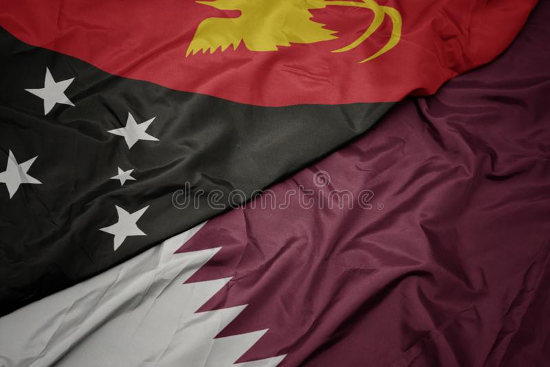 Waving colorful flag of qatar and national flag of Papua New Guinea. Macro stock image