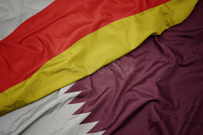 Waving colorful flag of qatar and national flag of south ossetia. Macro royalty free stock photo