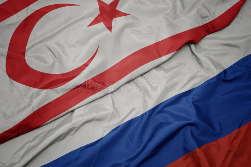 Waving colorful flag of russia and national flag of northern cyprus. Macro royalty free stock images