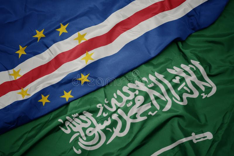 Waving colorful flag of saudi arabia and national flag of cape verde. Macro stock photo