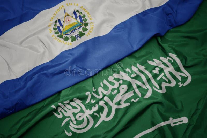 Waving colorful flag of saudi arabia and national flag of el salvador. Macro stock photos