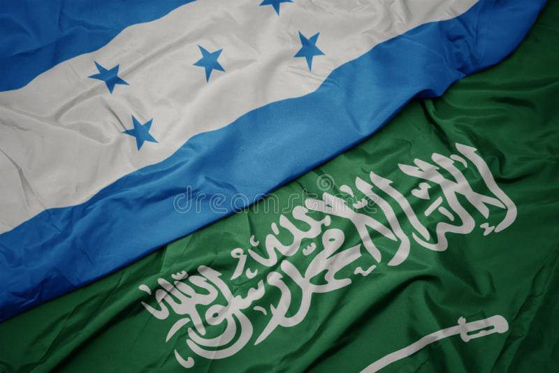 Waving colorful flag of saudi arabia and national flag of honduras. Macro stock image