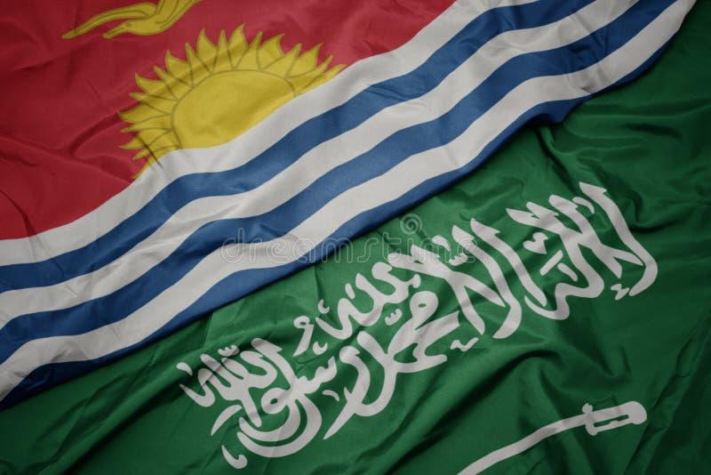 Waving colorful flag of saudi arabia and national flag of Kiribati. Macro royalty free stock photo