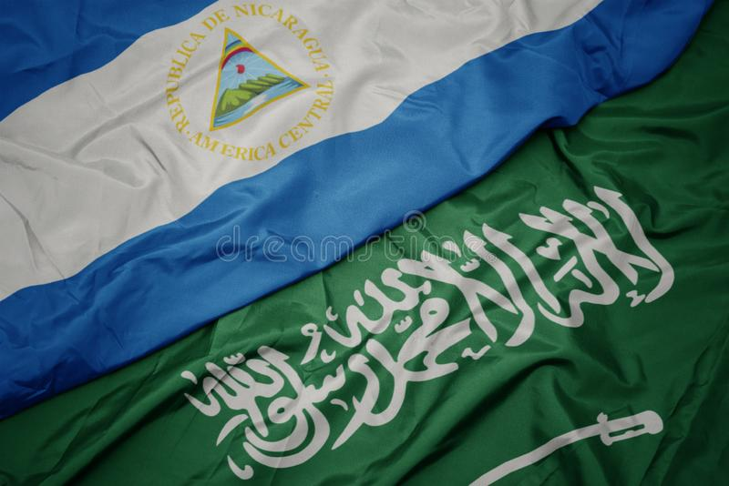 Waving colorful flag of saudi arabia and national flag of nicaragua. Macro stock photography