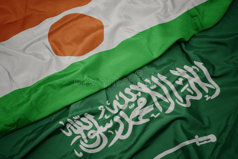 Waving colorful flag of saudi arabia and national flag of niger. Macro royalty free stock photo