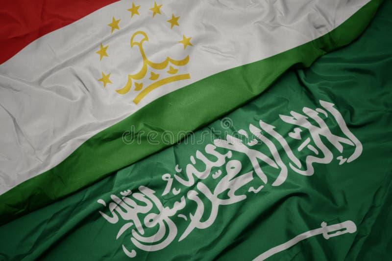Waving colorful flag of saudi arabia and national flag of tajikistan. Macro stock photos