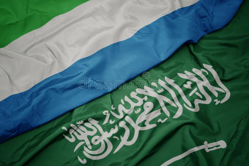 Waving colorful flag of saudi arabia and national flag of sierra leone. Macro stock photos