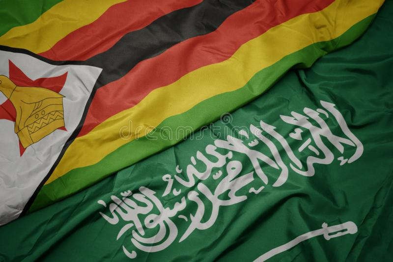 Waving colorful flag of saudi arabia and national flag of zimbabwe. Macro stock photo