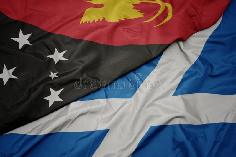 Waving colorful flag of scotland and national flag of Papua New Guinea. Macro royalty free stock photography
