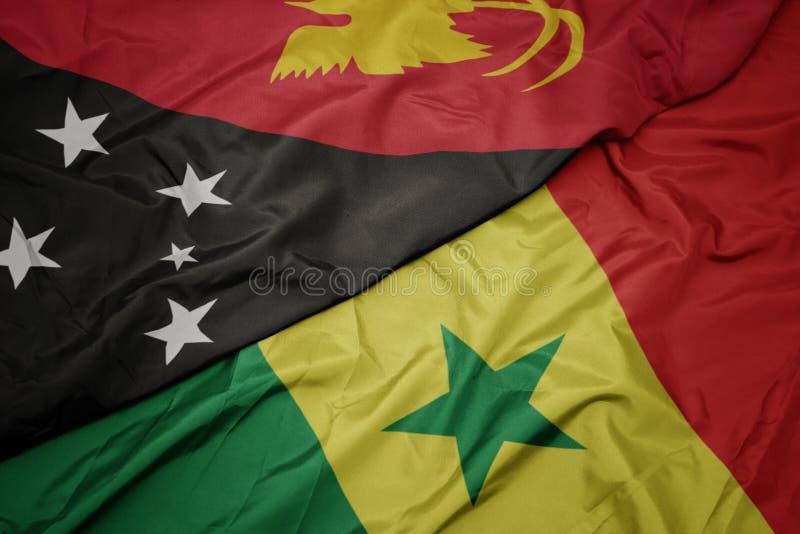 Waving colorful flag of senegal and national flag of Papua New Guinea. Macro stock photos