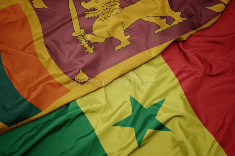 Waving colorful flag of senegal and national flag of sri lanka. Macro royalty free stock photo
