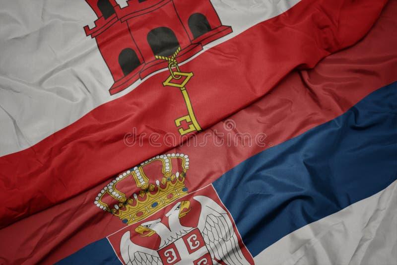 Waving colorful flag of serbia and national flag of gibraltar. Macro royalty free illustration