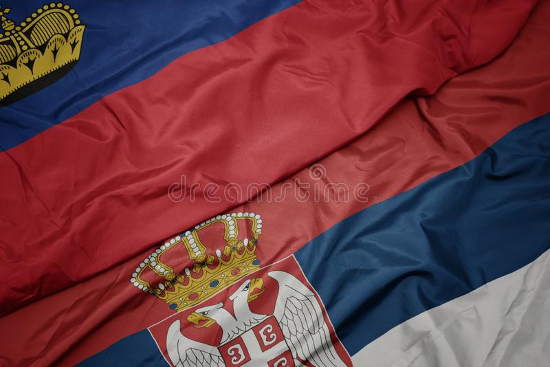 Waving colorful flag of serbia and national flag of liechtenstein. Macro stock illustration