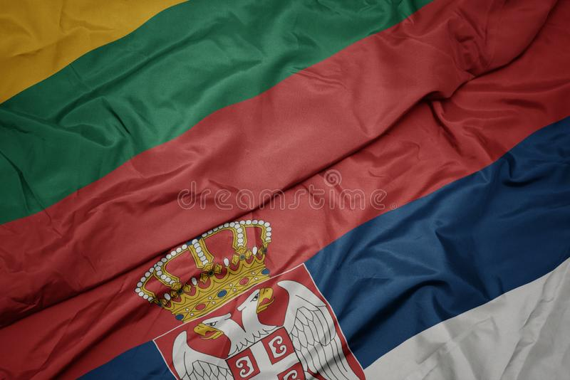 Waving colorful flag of serbia and national flag of lithuania. Macro royalty free illustration