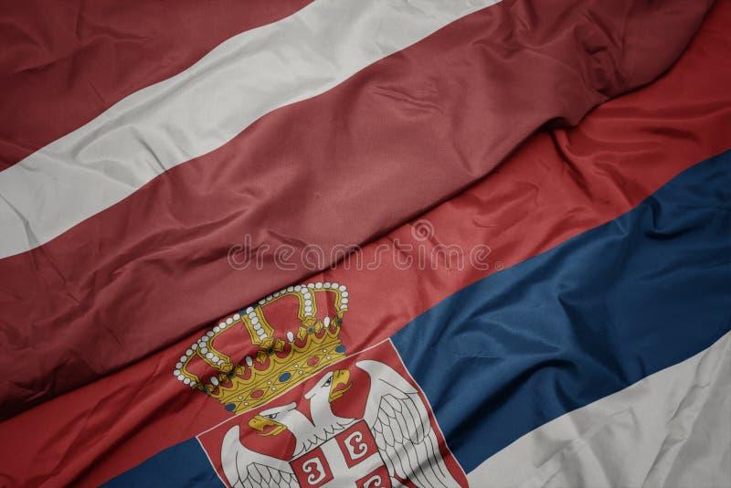 Waving colorful flag of serbia and national flag of latvia. Macro vector illustration