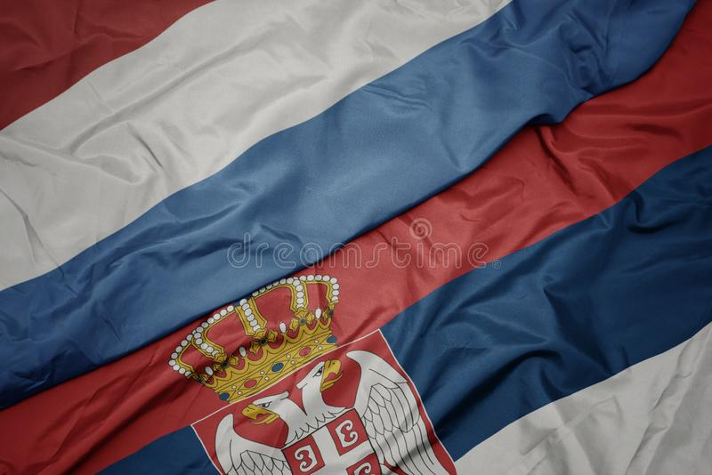 Waving colorful flag of serbia and national flag of luxembourg. Macro royalty free illustration