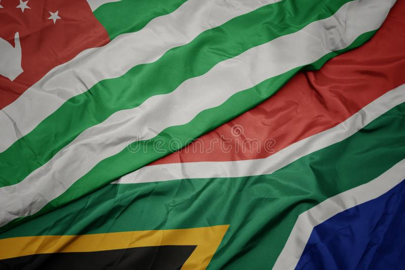 Waving colorful flag of south africa and national flag of abkhazia. Macro royalty free stock photography