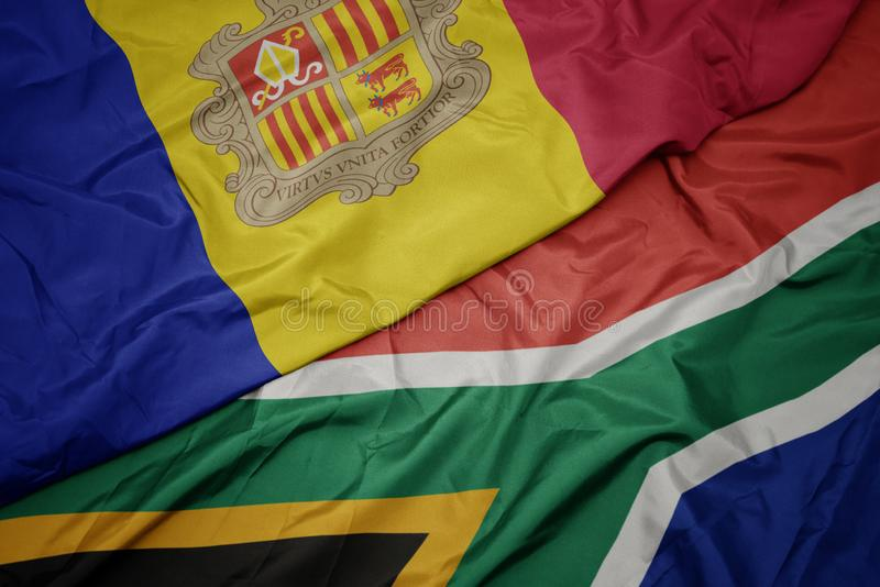 Waving colorful flag of south africa and national flag of andorra. Macro royalty free stock photography