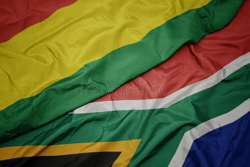 Waving colorful flag of south africa and national flag of bolivia. Macro royalty free stock photography