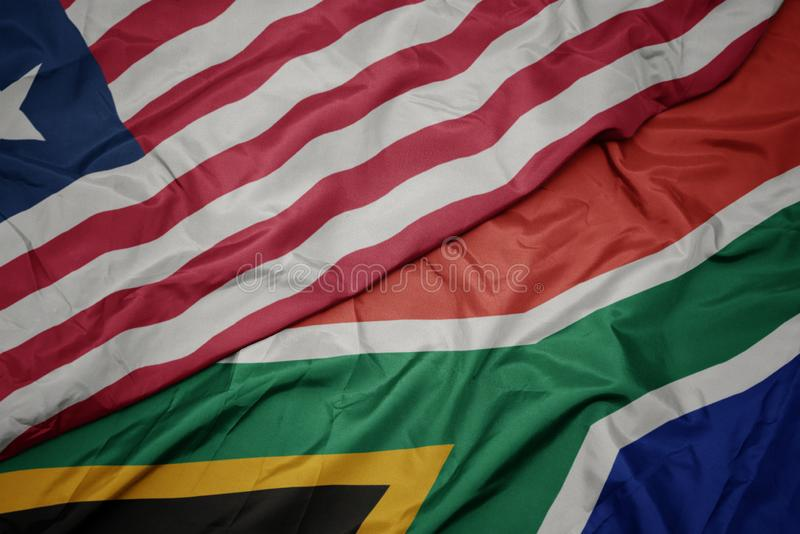 Waving colorful flag of south africa and national flag of liberia. Macro stock photos