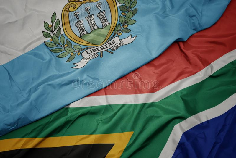 Waving colorful flag of south africa and national flag of san marino. Macro stock photo