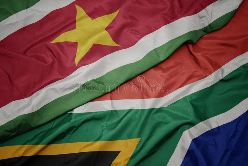 Waving colorful flag of south africa and national flag of suriname. Macro stock photo