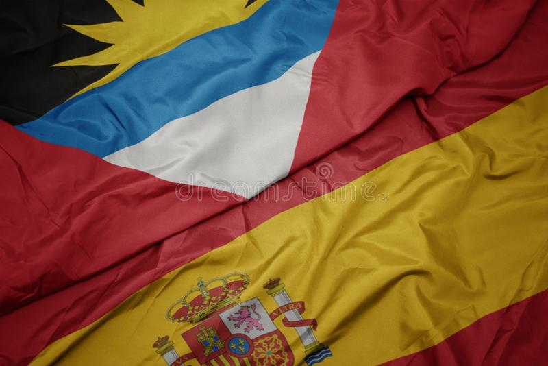 Waving colorful flag of spain and national flag of antigua and barbuda. Macro royalty free stock photo