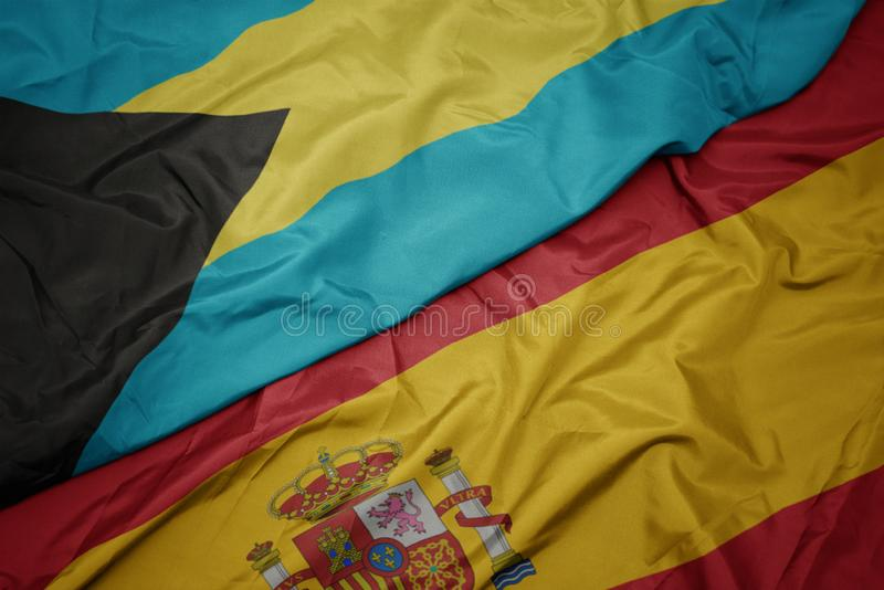 Waving colorful flag of spain and national flag of bahamas. Macro royalty free stock images