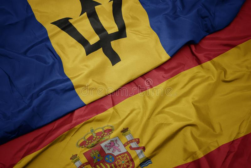 Waving colorful flag of spain and national flag of barbados. Macro royalty free stock image