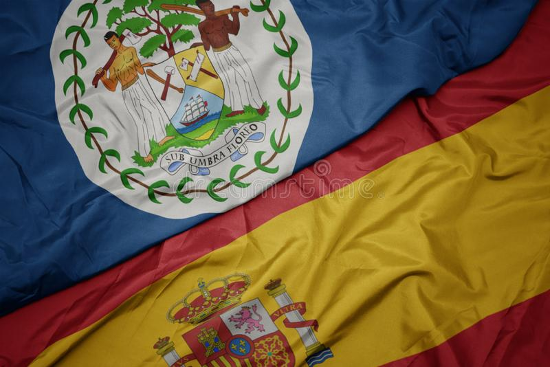 Waving colorful flag of spain and national flag of belize. Macro stock photos