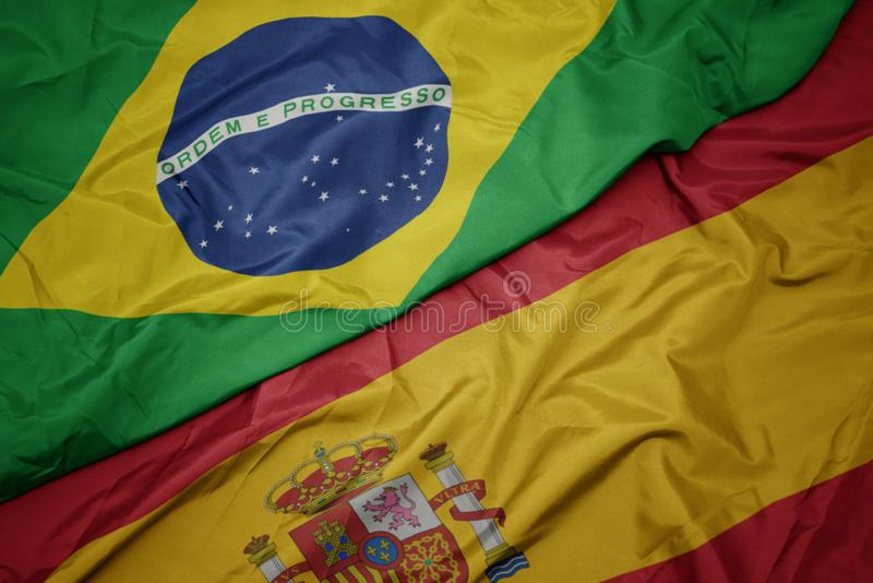 Waving colorful flag of spain and national flag of brazil. Macro royalty free stock photography