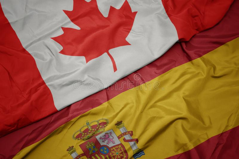 Waving colorful flag of spain and national flag of canada. Macro royalty free stock photo