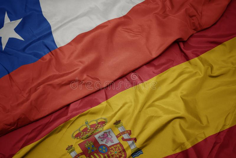 Waving colorful flag of spain and national flag of chile. Macro stock photos