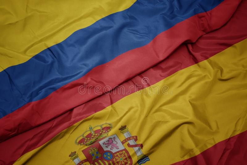 Waving colorful flag of spain and national flag of colombia. Macro royalty free stock images