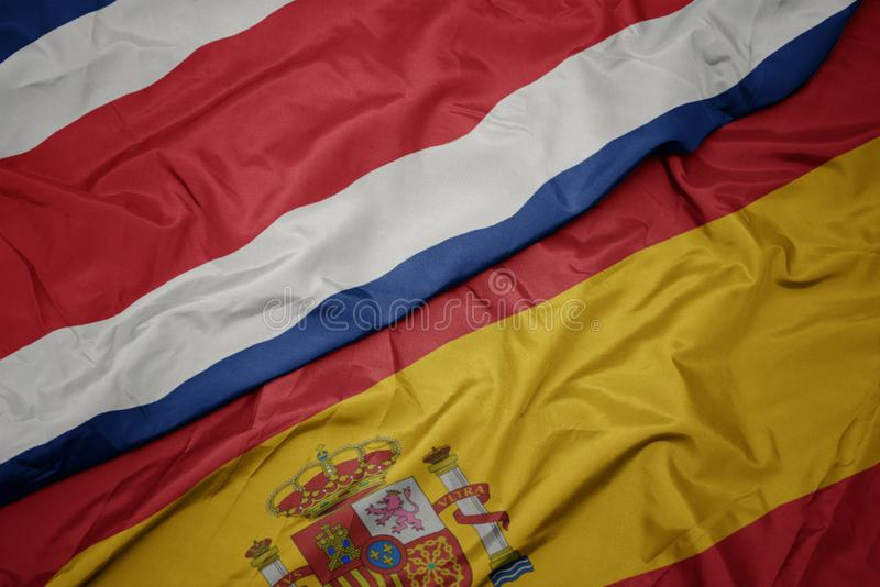 Waving colorful flag of spain and national flag of costa rica. Macro royalty free stock images