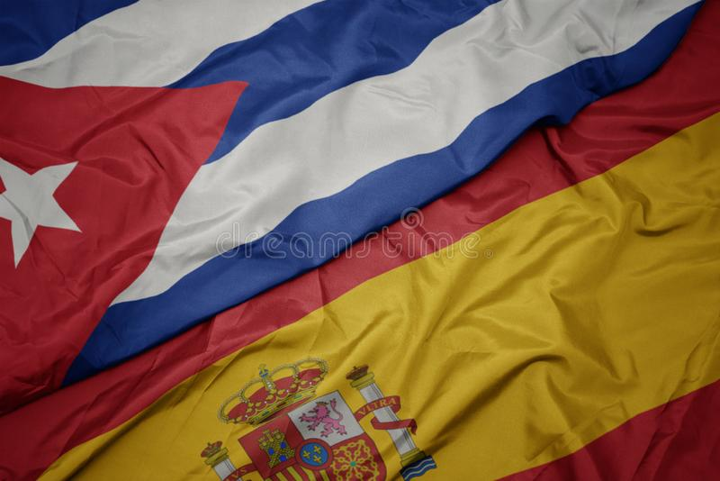 Waving colorful flag of spain and national flag of cuba. Macro royalty free stock photography