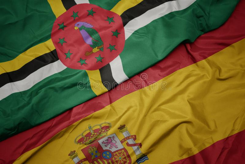 Waving colorful flag of spain and national flag of dominica. Macro stock images