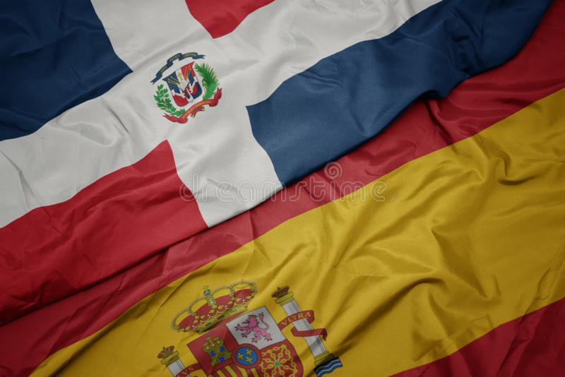 Waving colorful flag of spain and national flag of dominican republic. Macro royalty free stock images